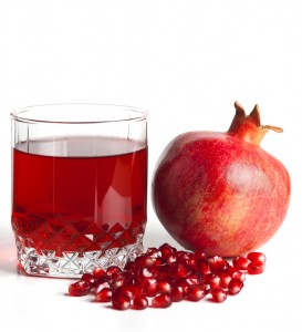 Glass filled by juice of a pomegranate and the seeds of a pomegr